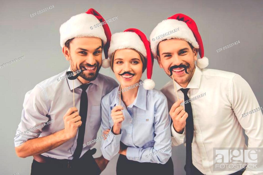 Stock Photo: Happy business people in Santa hats are holding party props on sticks, looking at camera and smiling, on gray background.