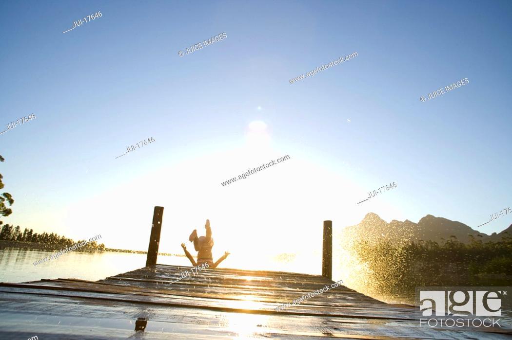 Stock Photo: Teenage boy jumping off dock into lake.