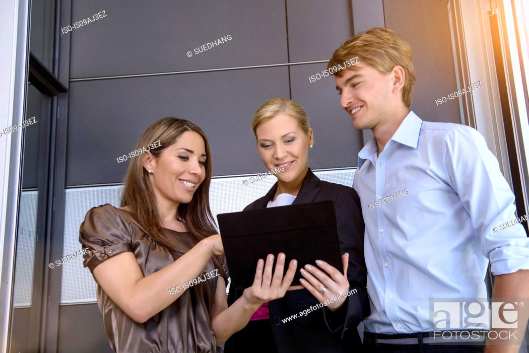 Stock Photo: Businesswomen and businessman using digital tablet for discussion.
