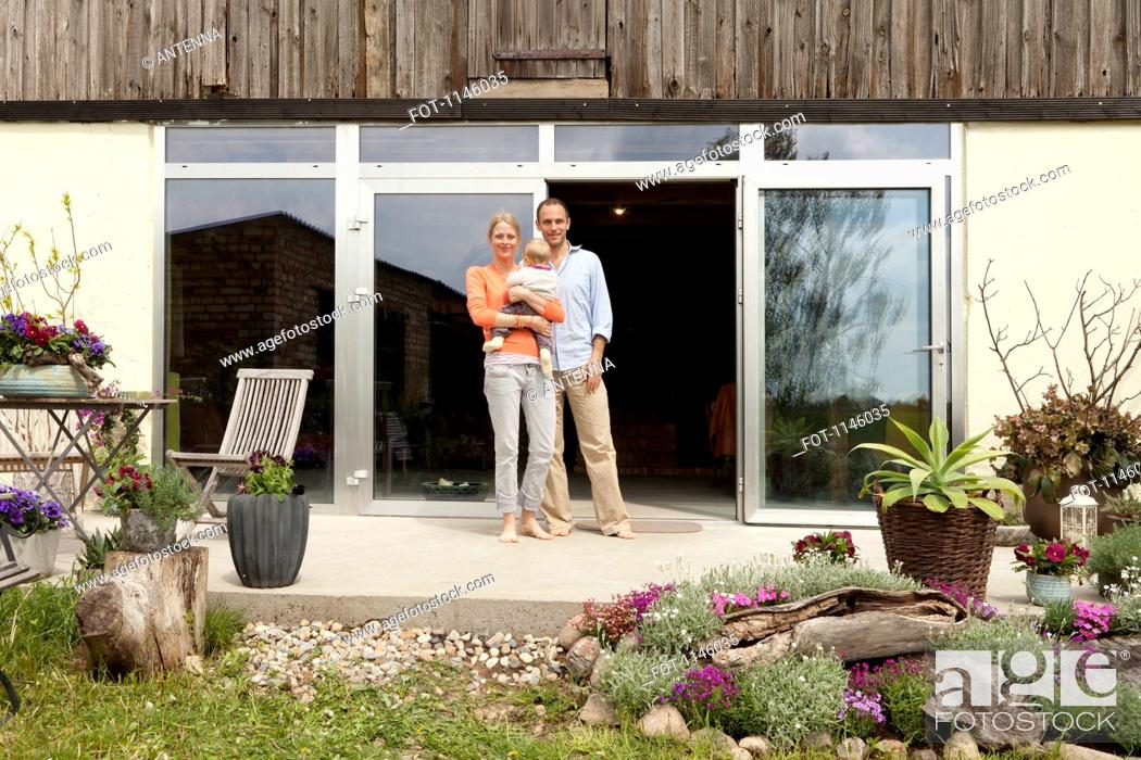 Stock Photo: A man and a woman holding a baby standing on the patio in front of their house.