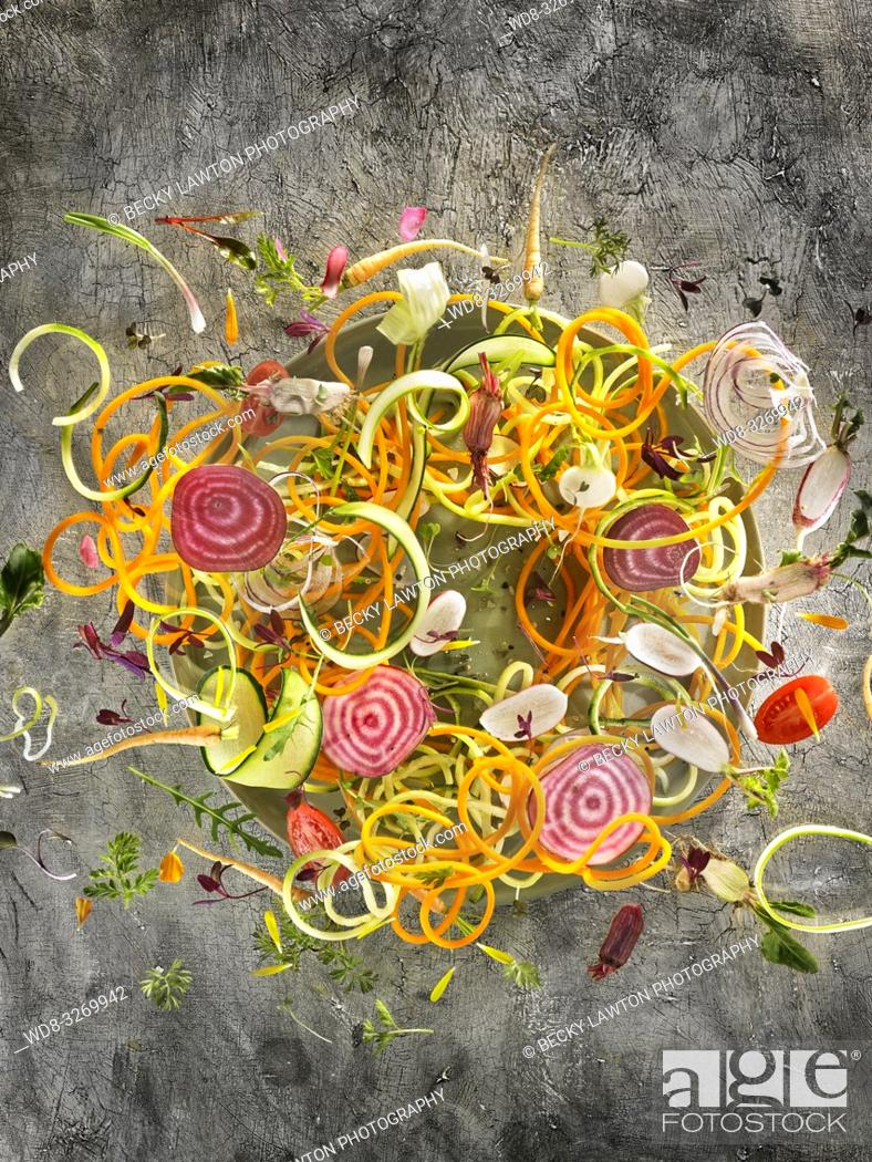 Stock Photo: Composition with vegetables and petals, flying over green plate and dark gray background.