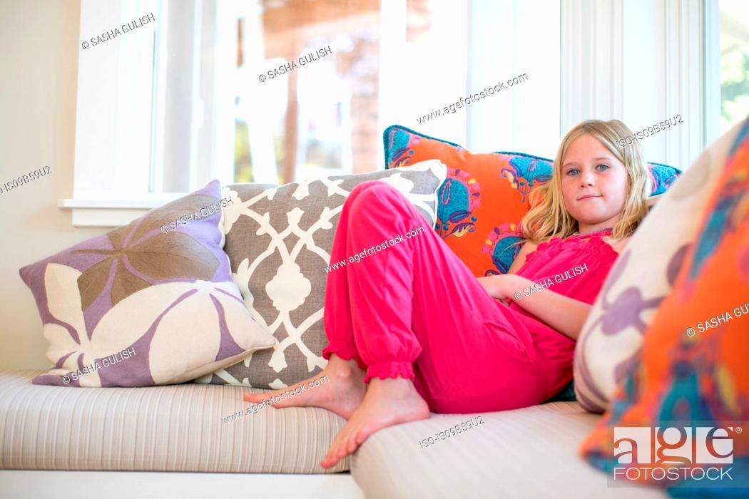 Stock Photo: Portrait of girl reclining on sofa.