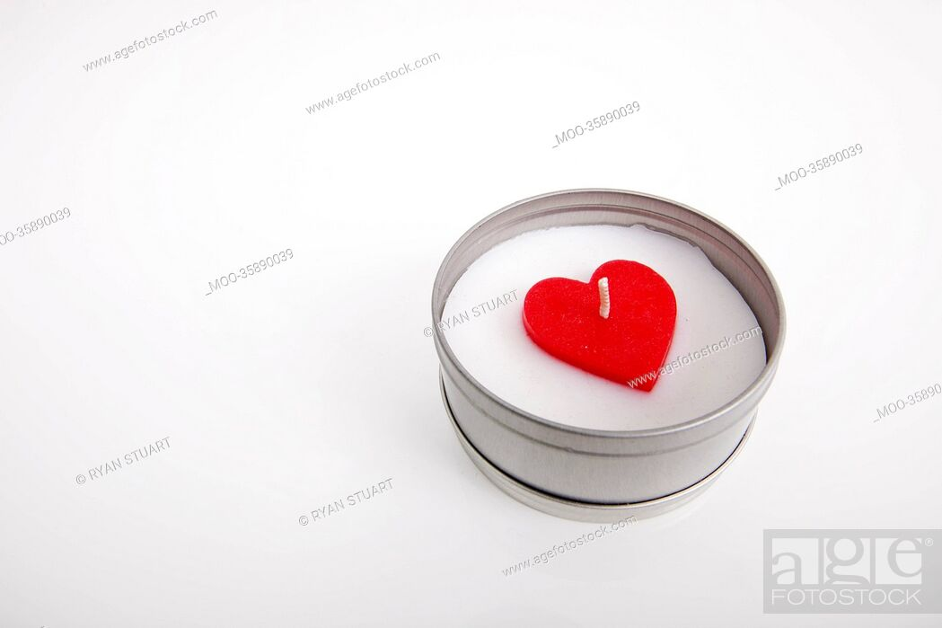 Stock Photo: Red and white candle with heart shape in container against white background.