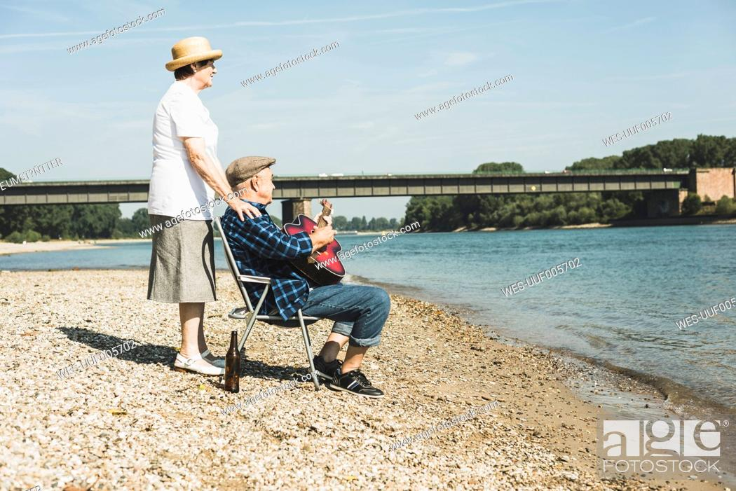 Imagen: Germany, Ludwigshafen, senior couple relaxing at riverside.