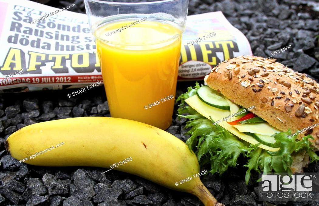Stock Photo: Breakfast including sandwich, orange juice and coffee and a newspaper to read.