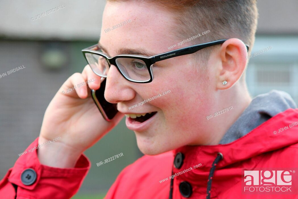 Stock Photo: Teenage boy with glasses smiling and talking on mobile phone.
