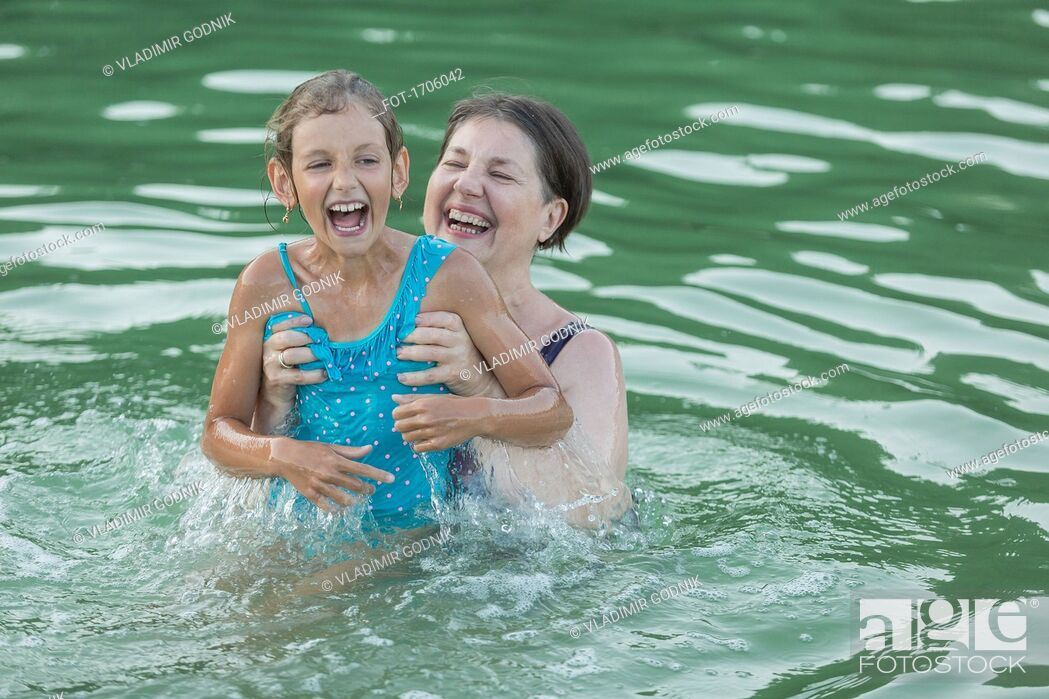 Stock Photo: Smiling grandmother enjoying with granddaughter while swimming in pool.