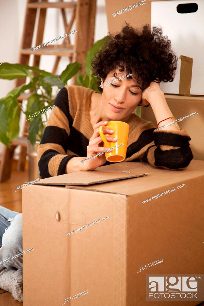 Stock Photo: A tired woman taking a coffee break while moving house.