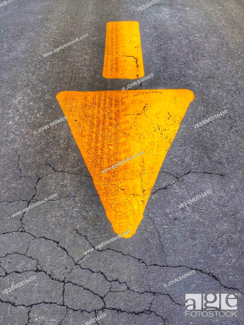 Stock Photo: Yellow arrow painted on asphalt with a tire track running through it.