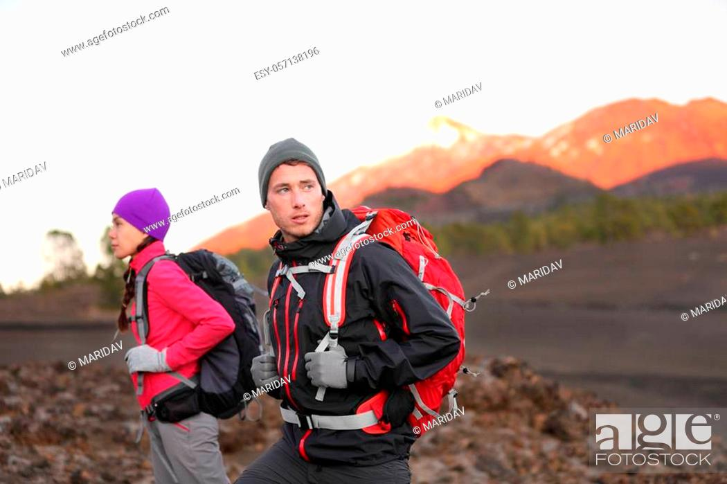 Stock Photo: Hiking people on mountain. Hiker couple walking with backpacks outdoors in high altitude. Young man hiker in focus trekking at sunset on volcano Teide, Tenerife.