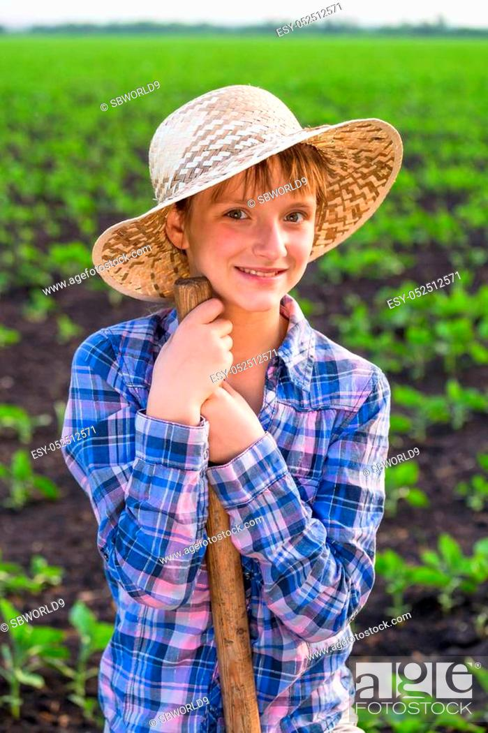 Stock Photo: Adorable girl standing with shovel on sunny rural landscape.
