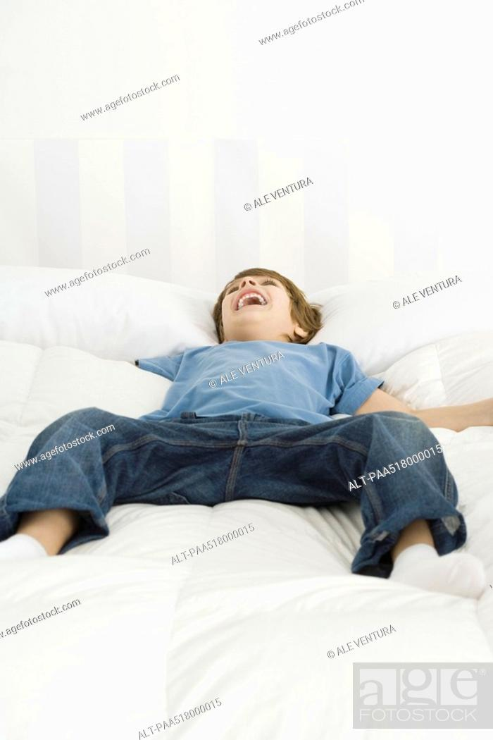 Stock Photo: Boy lying on bed, laughing.