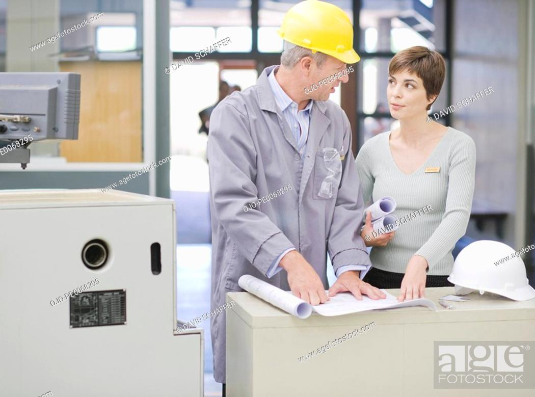 Stock Photo: Businesswoman reviewing blueprints with construction worker.