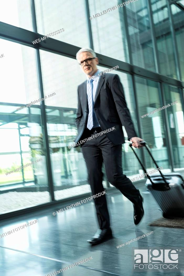 Stock Photo: Germany, Stuttgart, Businessman pulling luggage in office building.