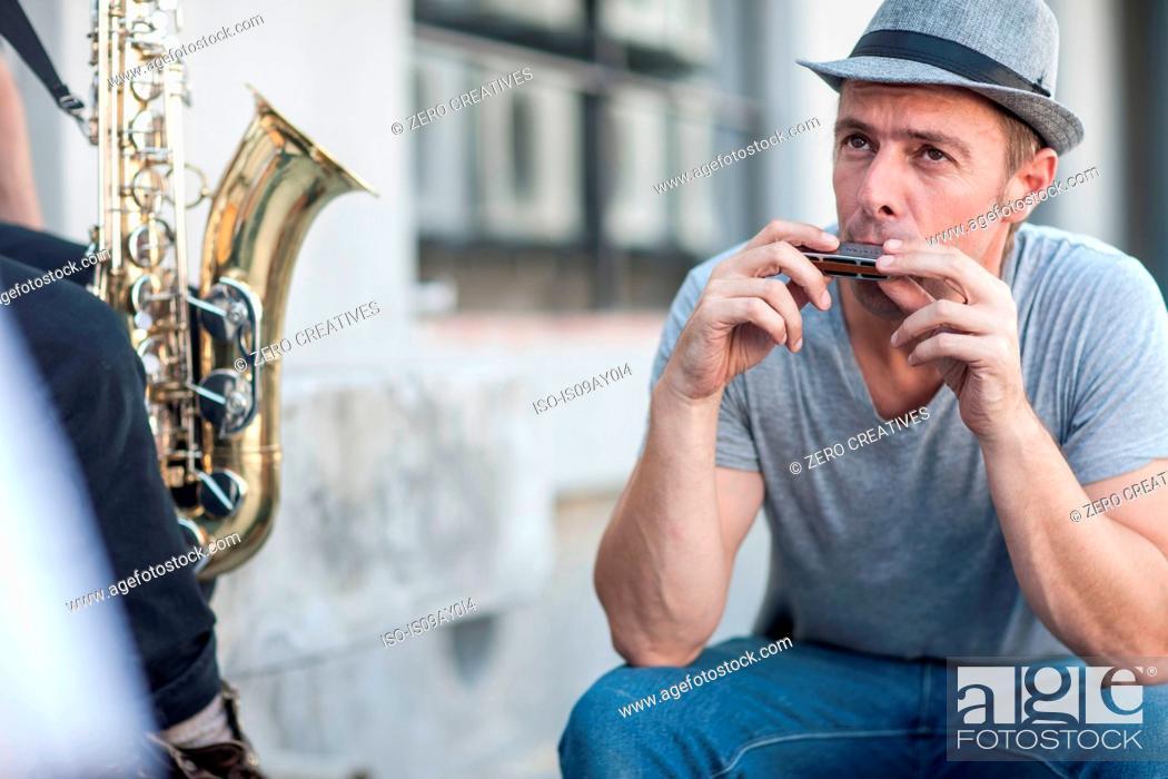 Imagen: Street musician playing harmonica.