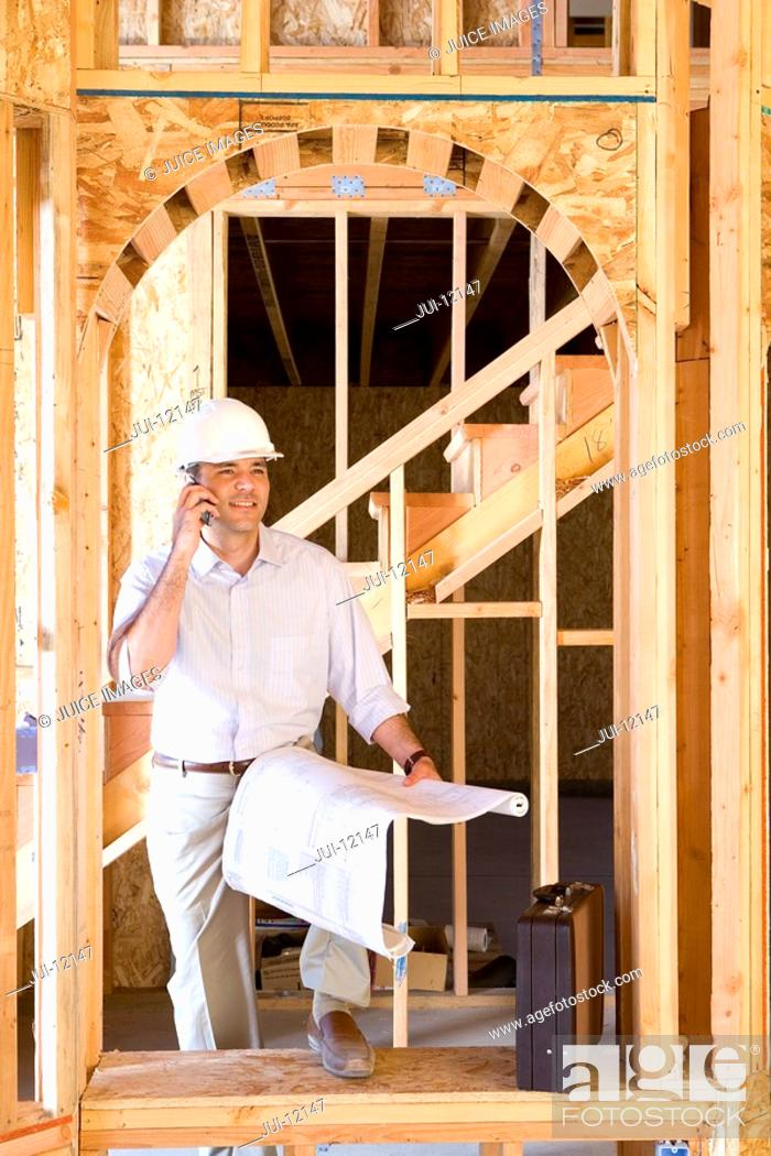 Stock Photo: Architect with blueprint using mobile phone in partially built house.