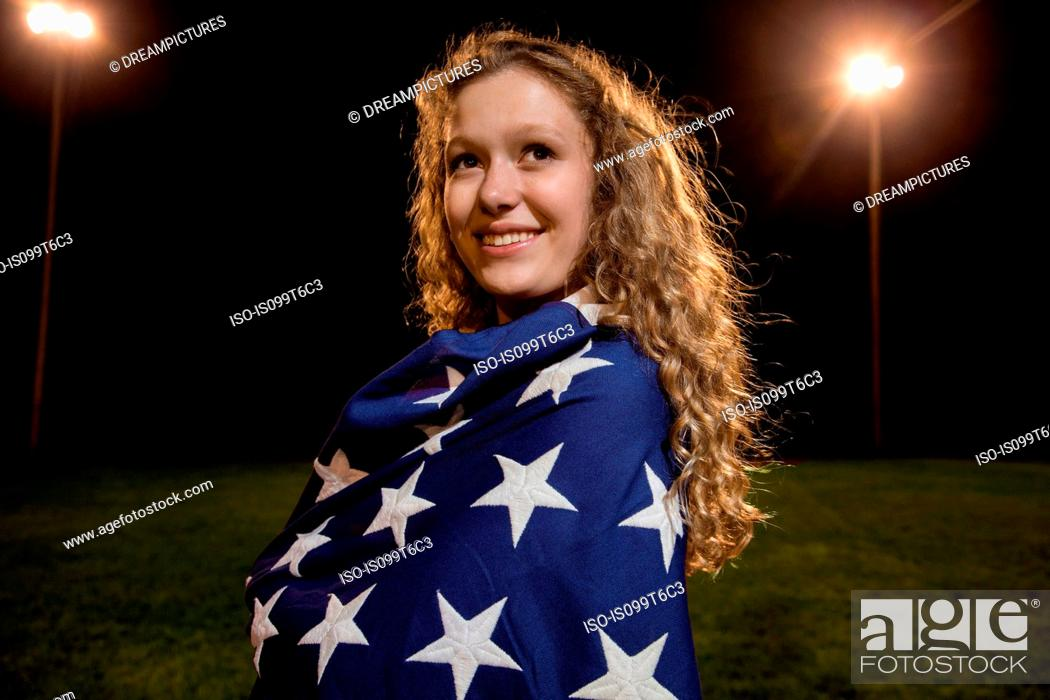 Imagen: Girl wrapped in american flag at night.