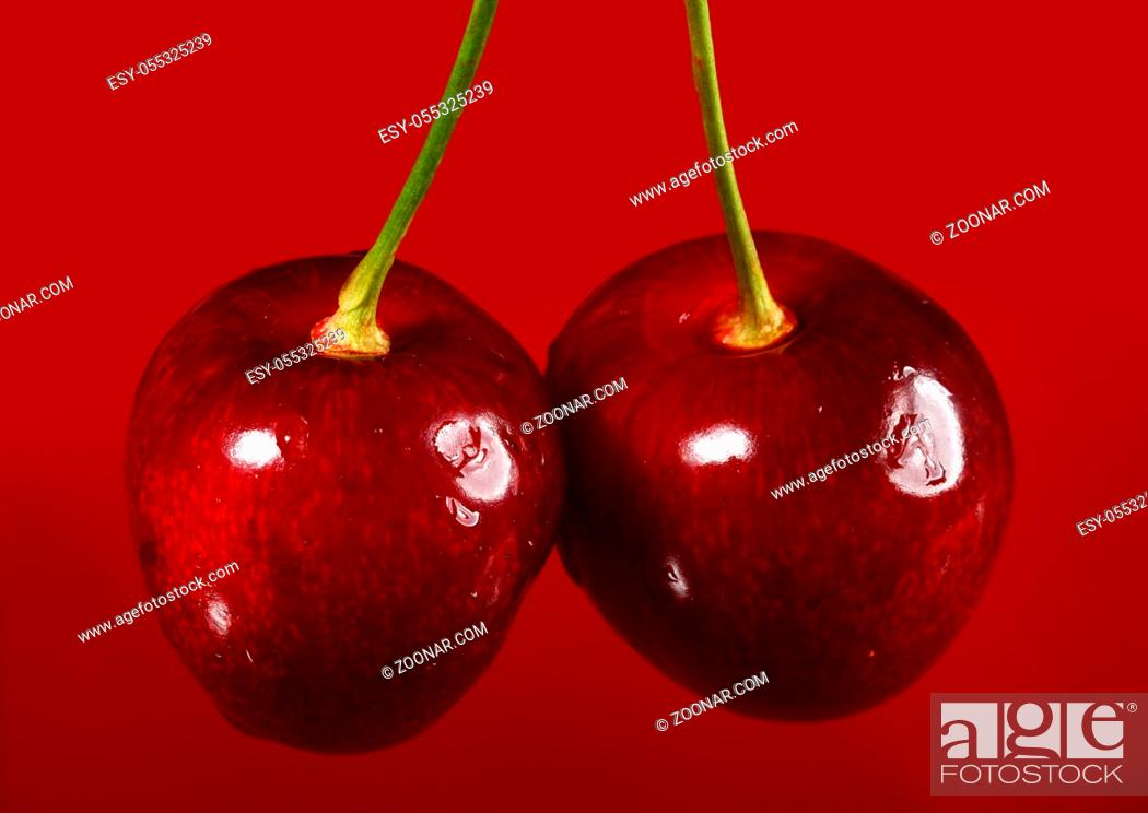 Stock Photo: Close up of cherry against red background.