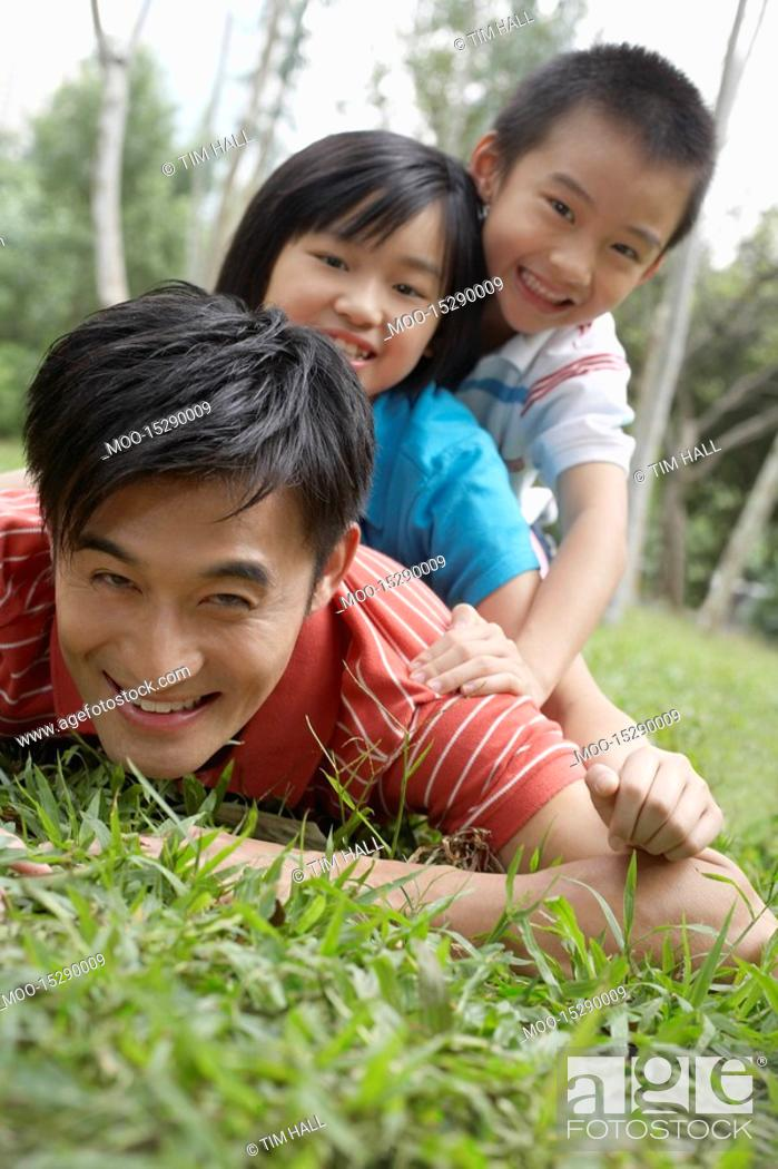 Stock Photo: Father with son and daughter 7-9 lying in grass in park.