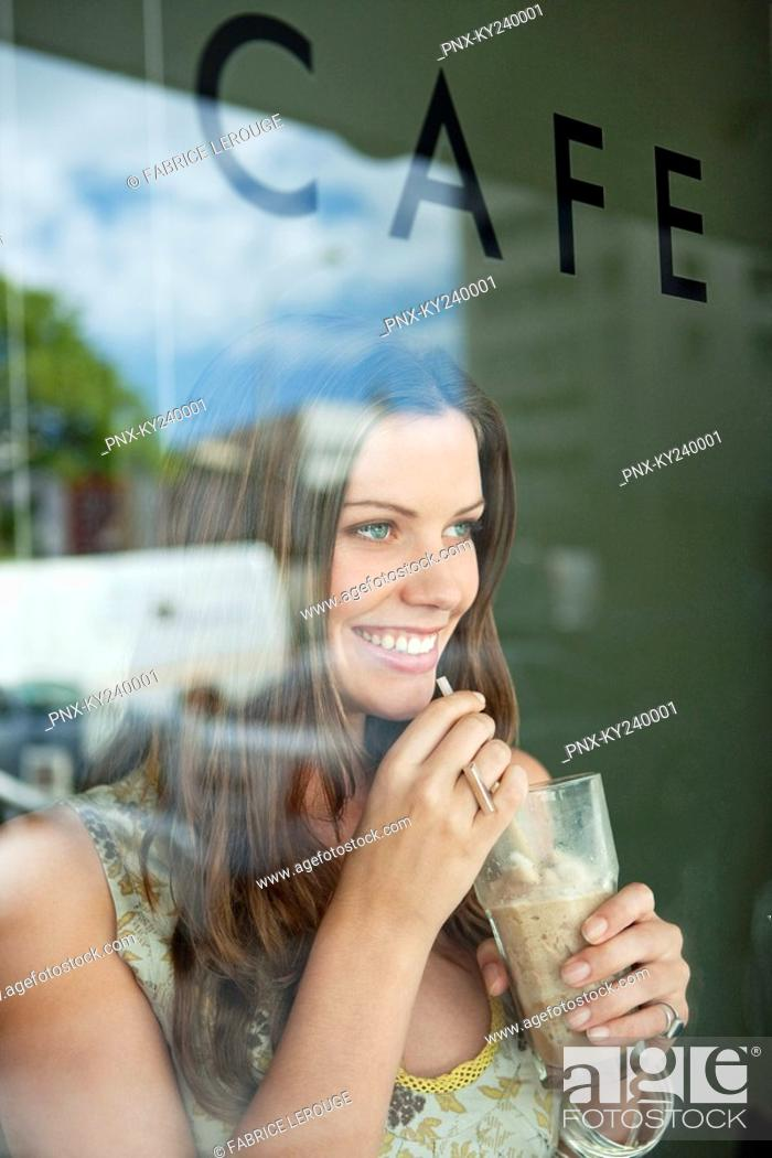 Stock Photo: Woman drinking chocolate milkshake in a cafe.