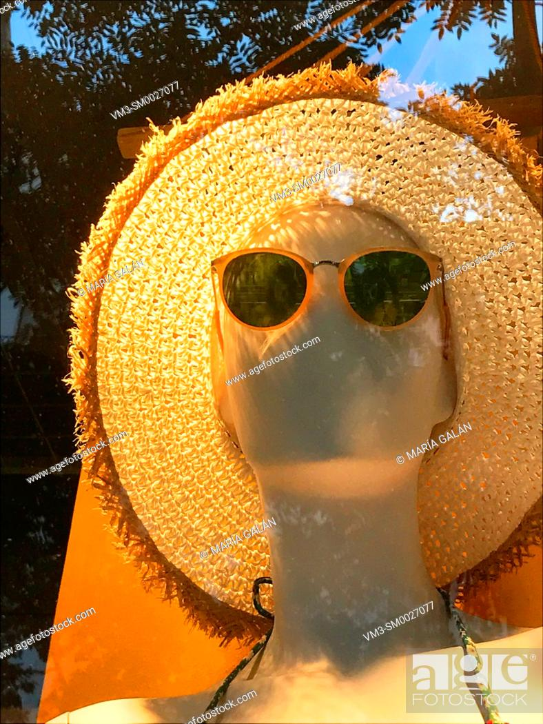 Stock Photo: Mannequin in a shop window wearing sunglasses and straw hat.