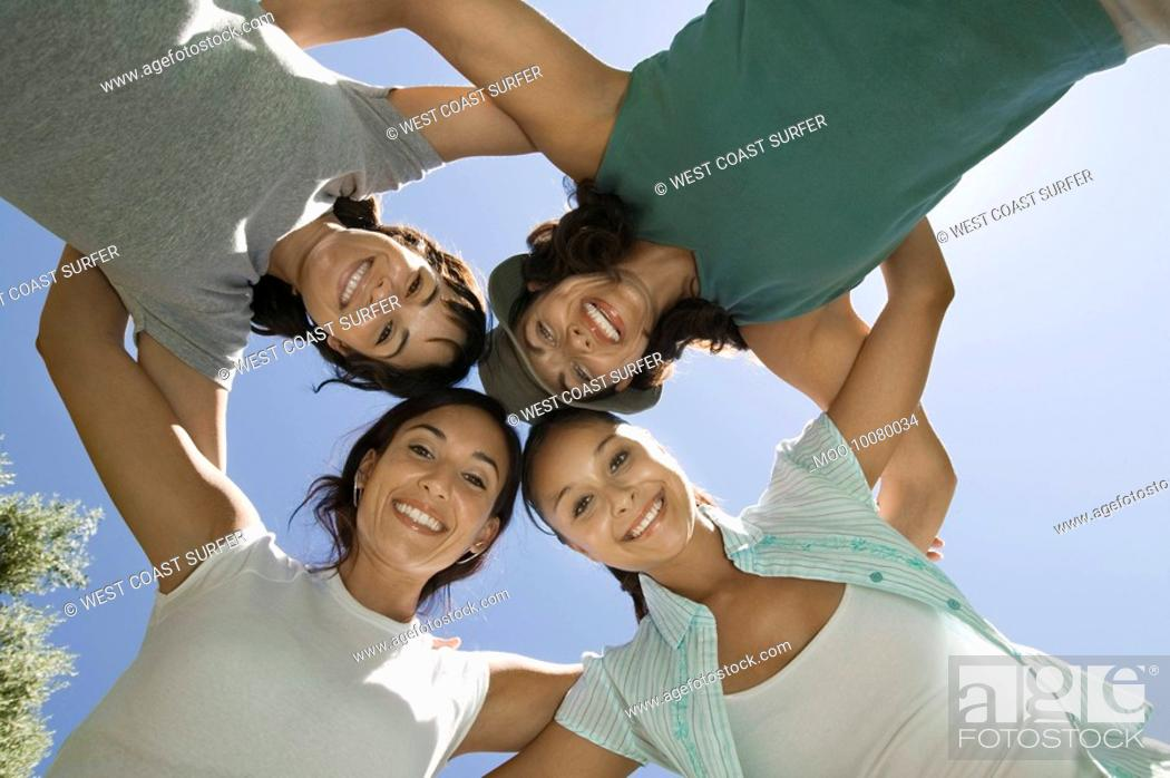 Stock Photo: Four women in huddle view from below.