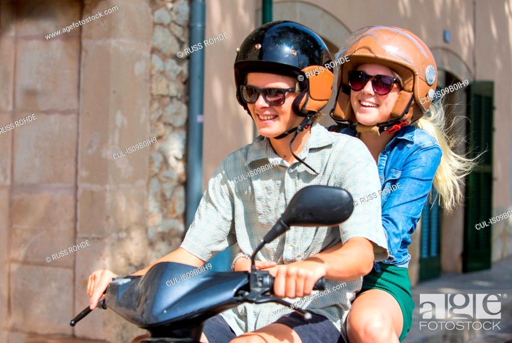 Stock Photo: Young couple riding moped together through village, Majorca, Spain.