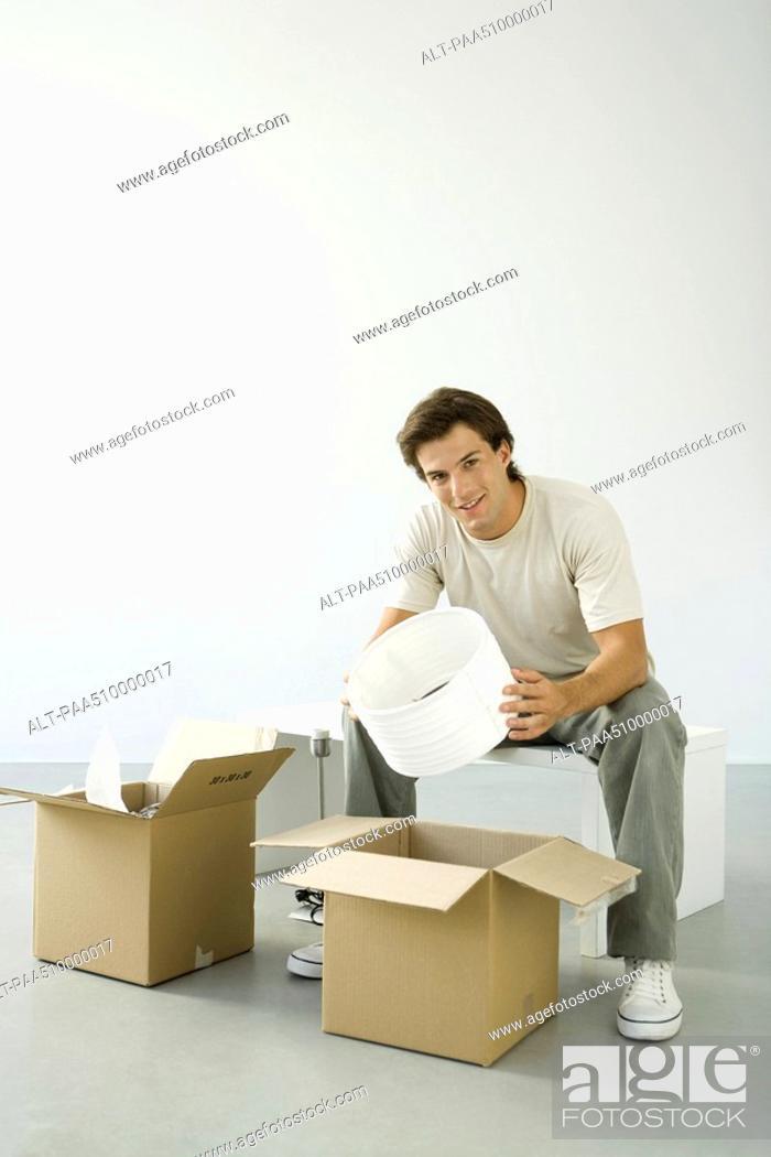 Stock Photo: Man unpacking boxes, holding lampshade, smiling at camera.