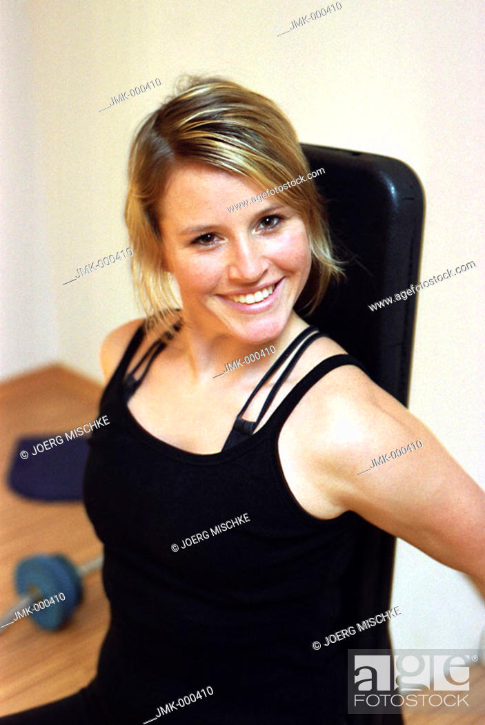 Stock Photo: Young woman at the gym, fitness center, doing some exercise, training.