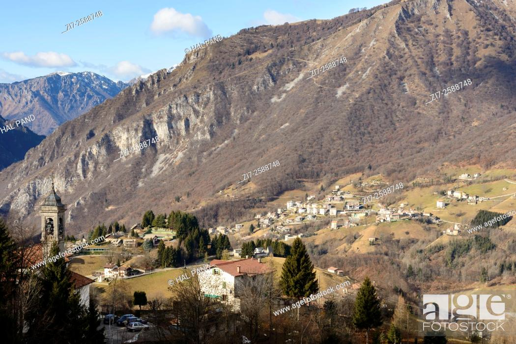 Stock Photo: landscape with mountain village near the rocky slope of Menna peak in Bergamo mountains in a winter with little snow , shot in bright winter light.