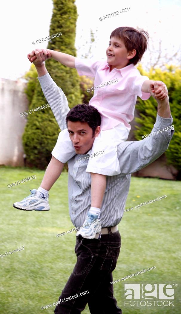 Stock Photo: Man carrying a little boy on his shoulders.