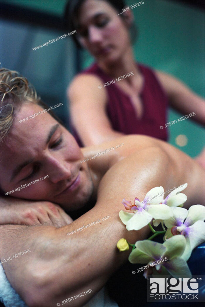 Stock Photo: physical therapist is giving a massage to a young man.