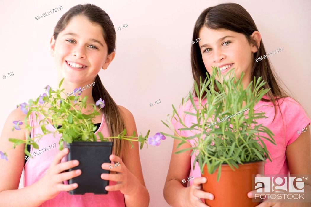 Caucasian twin sisters holding potted plants, Stock Photo, Picture