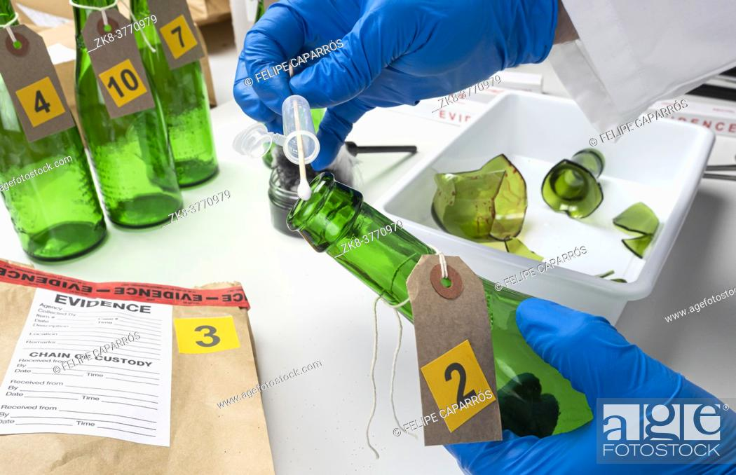 Stock Photo: Police expert gets blood sample from a green glass bottle in Criminalistic Lab, conceptual image.