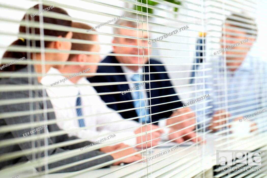 Stock Photo: Business team sitting behind blinds.