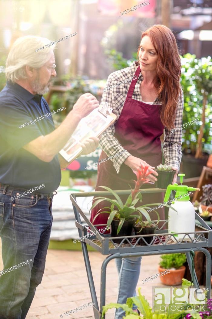 Imagen: Manger and gardener discussing in garden center.