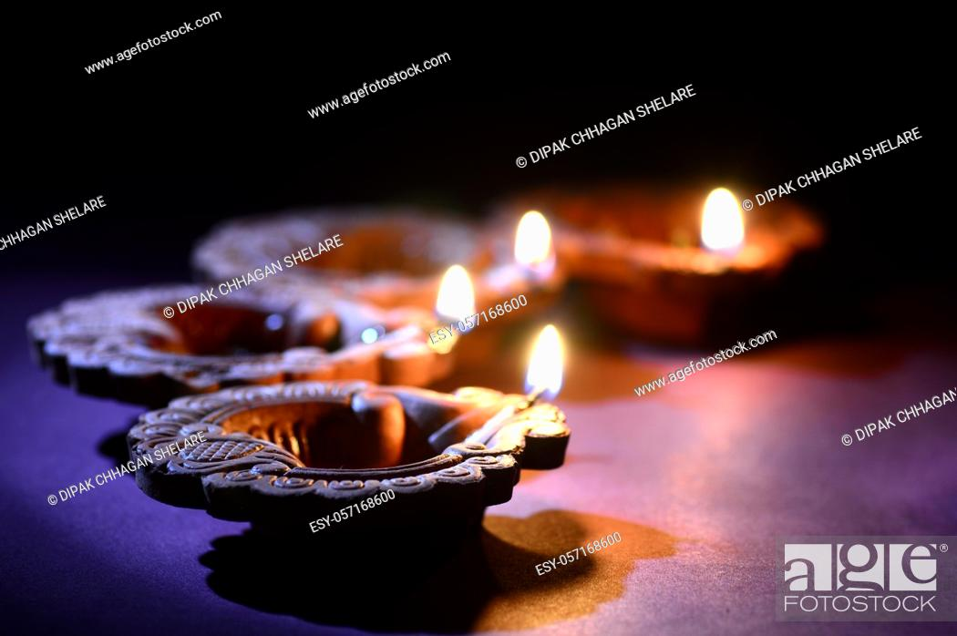 Stock Photo: Colorful clay Diya (Lantern) lamps lit during Diwali celebration. Greetings Card Design Indian Hindu Light Festival called Diwali.