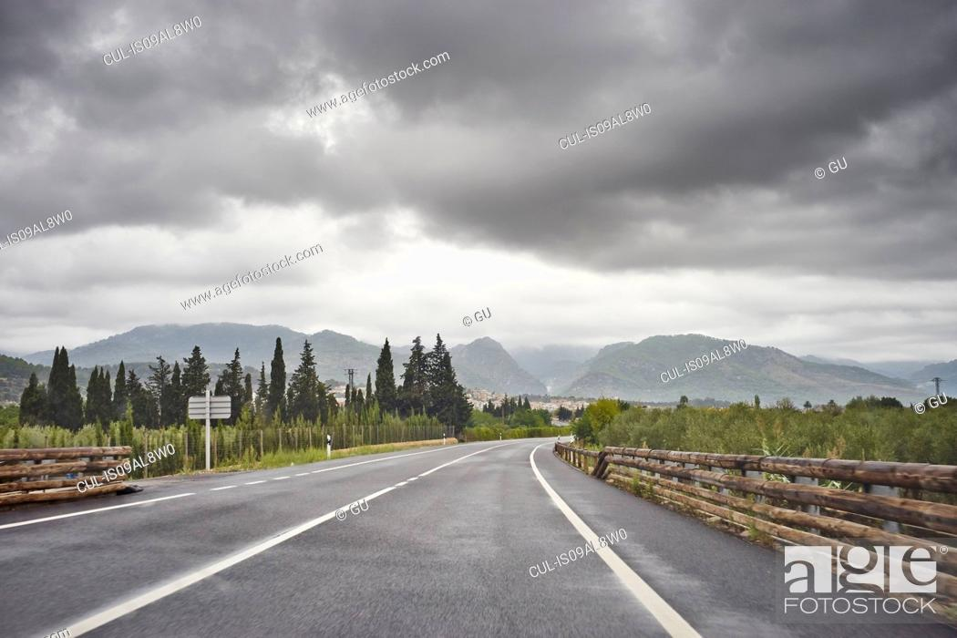 Stock Photo: Empty road through rural scene, grey clouds above, Majorca, Spain.