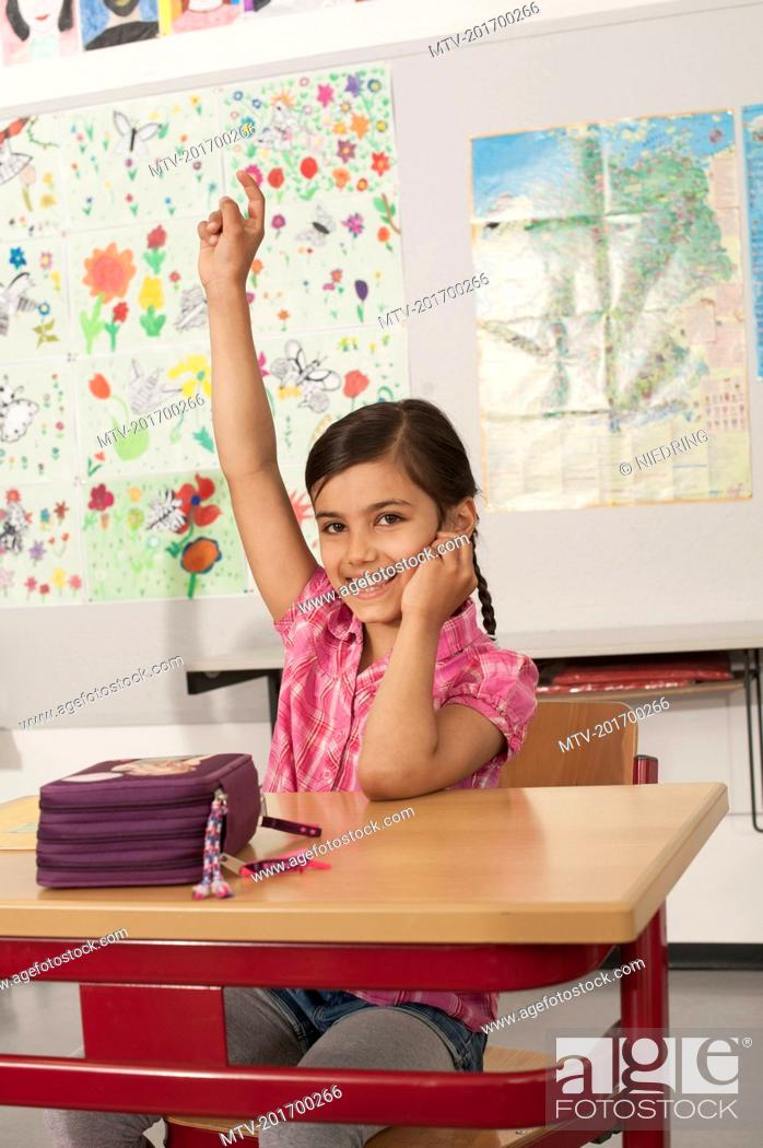 Stock Photo: Portrait of a schoolgirl with hand raised in classroom, Munich, Bavaria, Germany.