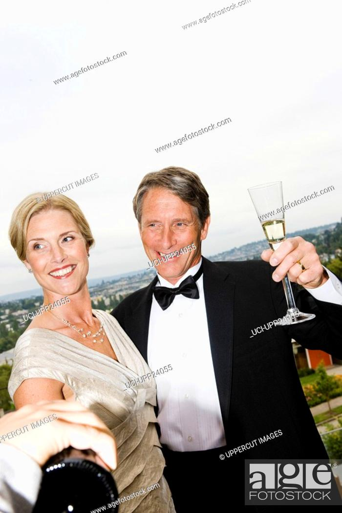 Stock Photo: Couple in eveningwear drinking champagne on balcony.