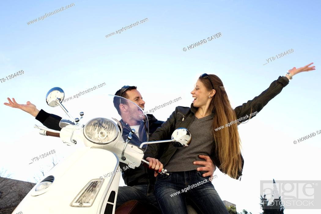 Stock Photo: Couple sitting on a motor scooter and raising their arms in the air.