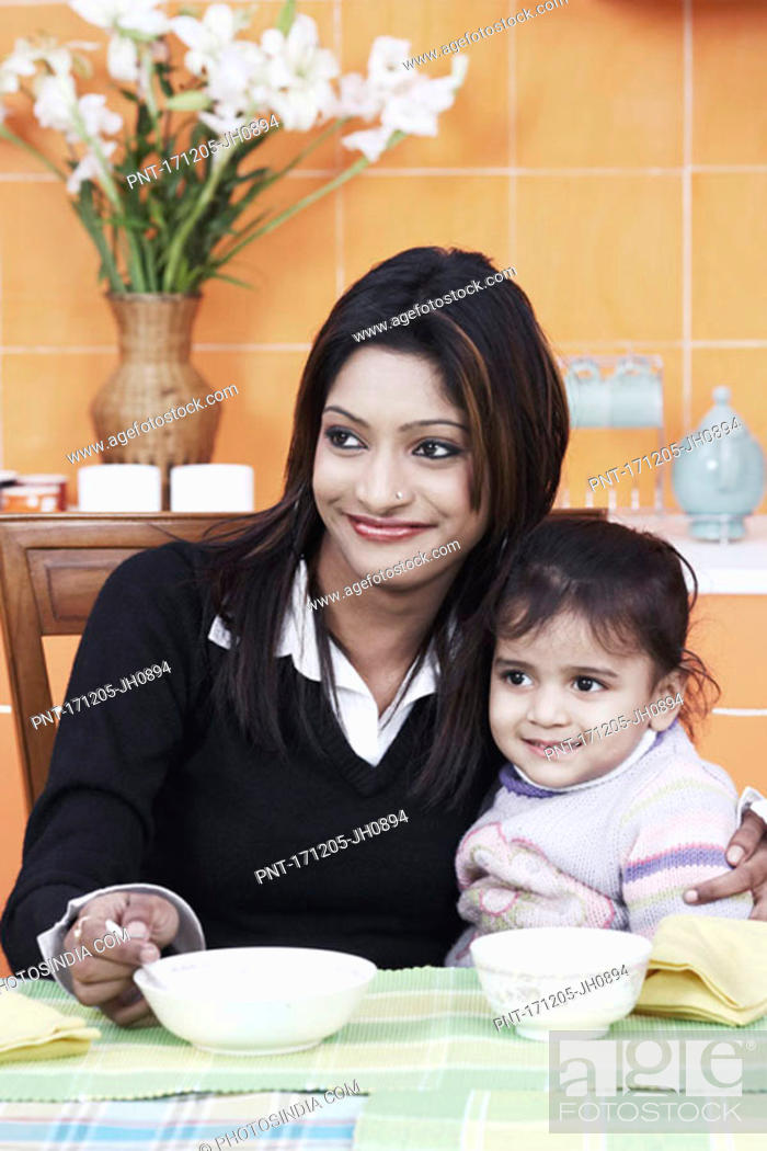 Stock Photo: Close-up of a mother with her daughter at the dining table.