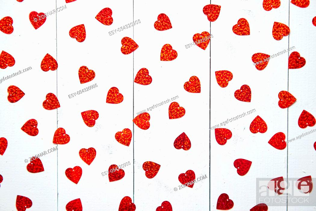 Stock Photo: Valentine's Day decoration composition. Heart shaped red sequins placed on white wooden table. Romantic background. Flat lay, top view.