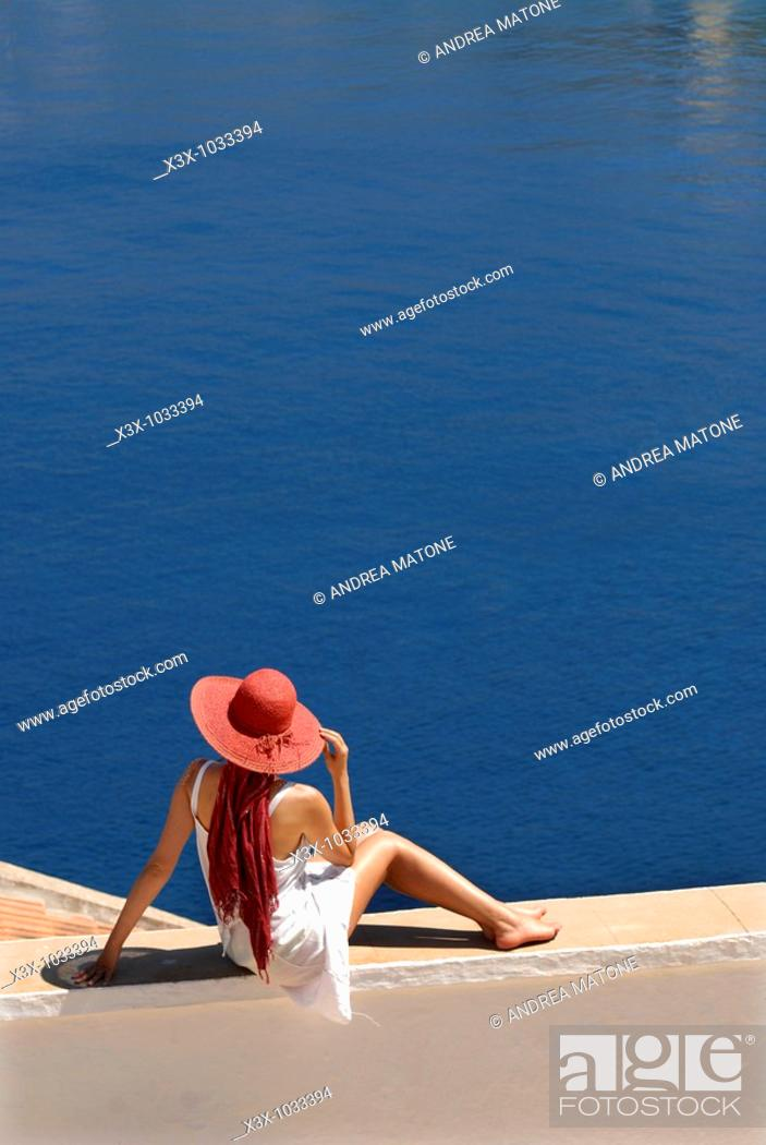 Stock Photo: Woman sitting in front of a sweeping view of the sea in the island of Symi Greece.