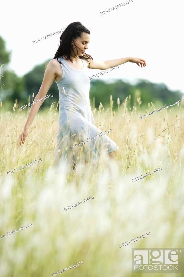 Stock Photo: Teen girl walking through field.