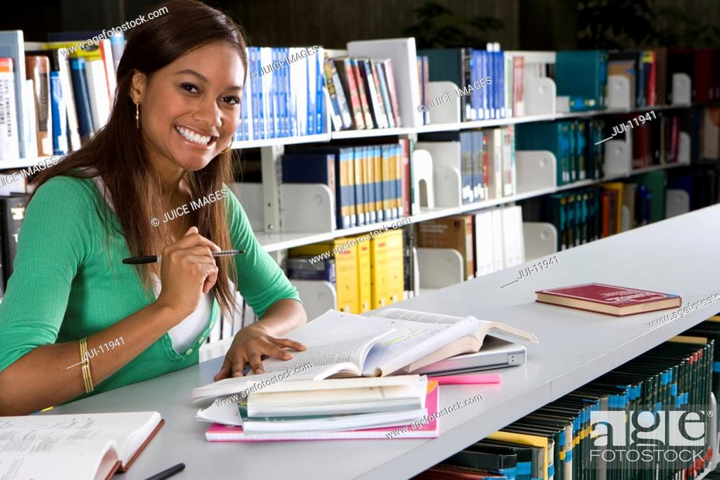 Stock Photo: Young woman studying in library, smiling, portrait.