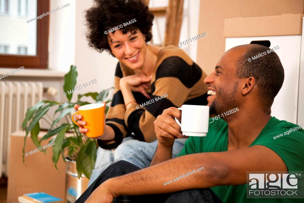 Stock Photo: A laughing couple taking a coffee break while moving house, close-up.