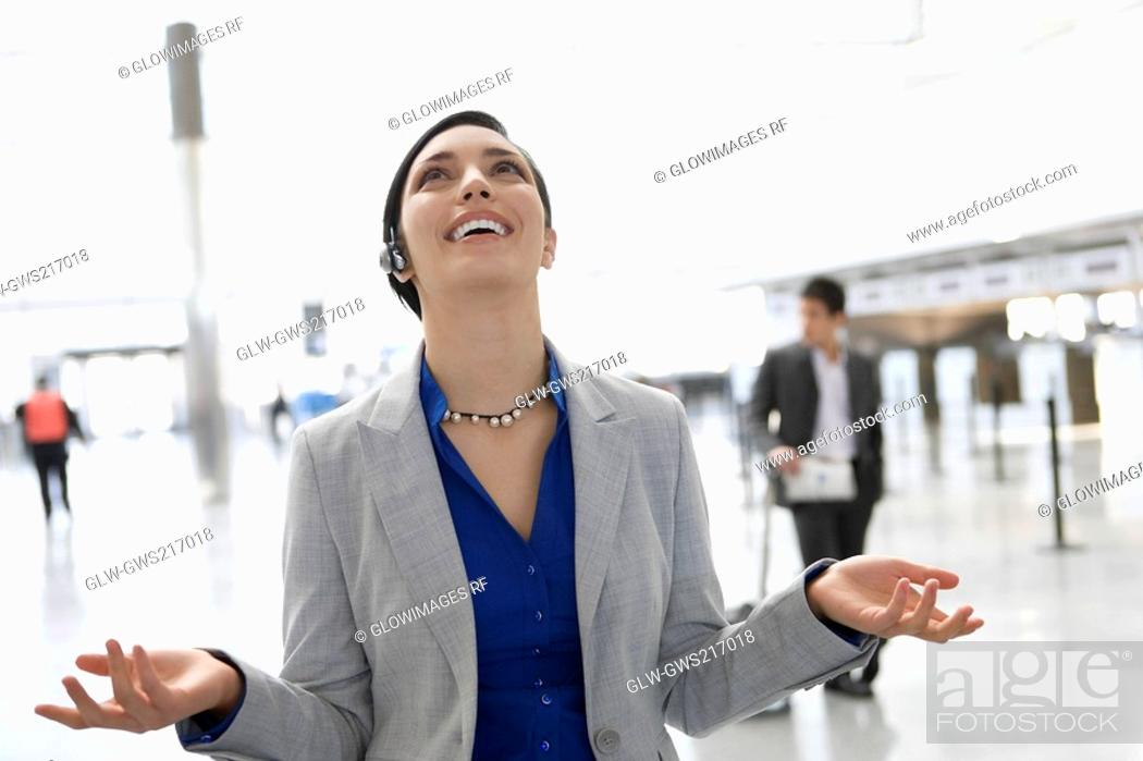 Stock Photo: Businesswoman laughing in a hands free device at an airport lounge.