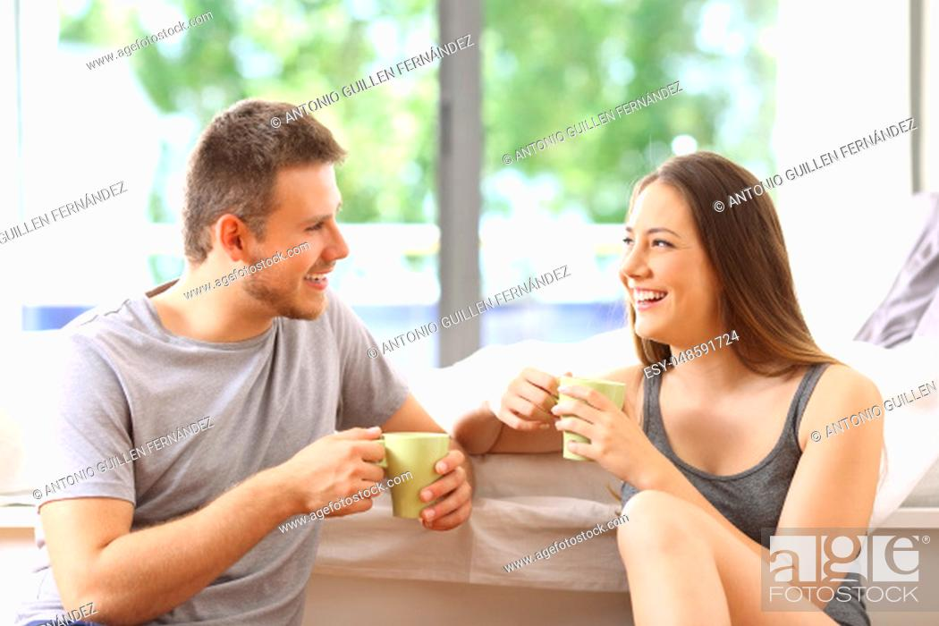 Stock Photo: Happy couple talking and having breakfast in an hotel room or home with a green background outdoors.
