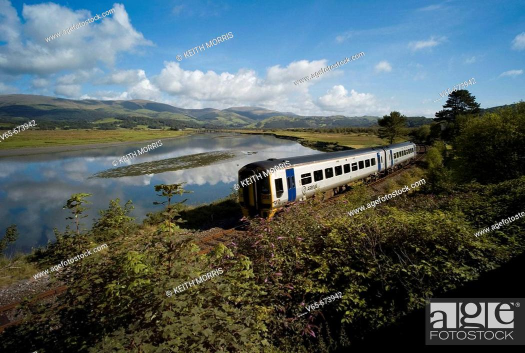 Stock Photo: Arriva Trains Wales diesel train at Dovey Junction near Machynlleth Powys, with the Dyfi River behind and the hills and mountains of Snowdonia National Park in.